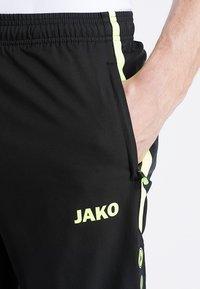 JAKO - STRIKER - Pantalones deportivos - schwarz/neongelb - 4