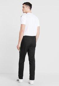 JAKO - STRIKER - Pantalones deportivos - schwarz/neongelb - 2