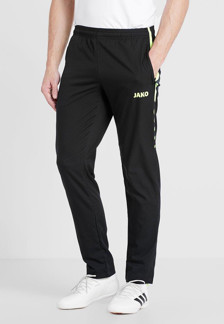 JAKO - STRIKER - Pantalones deportivos - schwarz/neongelb