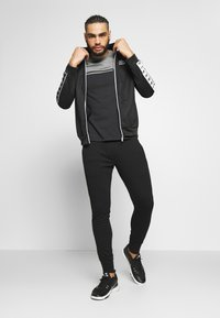 Jack & Jones Performance - JJWILL JJZSWEAT PANTS - Tracksuit bottoms - black - 1