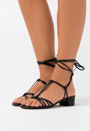 KNOTTED TSTRAP FLORA - Sandaalit nilkkaremmillä - black