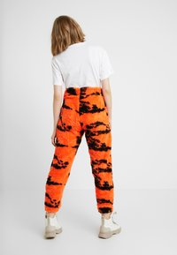 Jaded London - TIE DYE TROUSERS - Pantaloni sportivi - orange/black