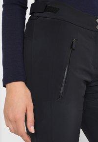 Kjus - WOMEN FORMULA PANTS - Täckbyxor - black - 4