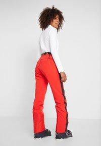 Kjus - WOMEN MADRISA PANTS - Täckbyxor - fiery red/black - 2
