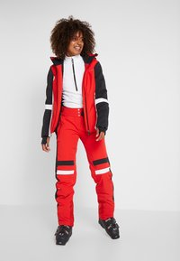 Kjus - WOMEN MADRISA PANTS - Ski- & snowboardbukser - fiery red/black - 1