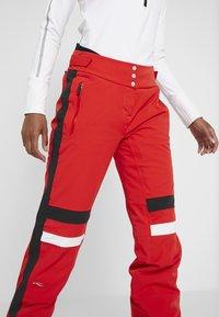 Kjus - WOMEN MADRISA PANTS - Täckbyxor - fiery red/black - 4