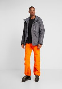 Kjus - MEN FORMULA PANTS - Pantalon de ski - orange - 1