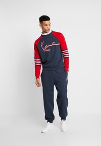 Karl Kani - RETRO TRACKPANTS - Tracksuit bottoms - navy - 1