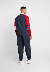 Karl Kani - RETRO TRACKPANTS - Tracksuit bottoms - navy - 2