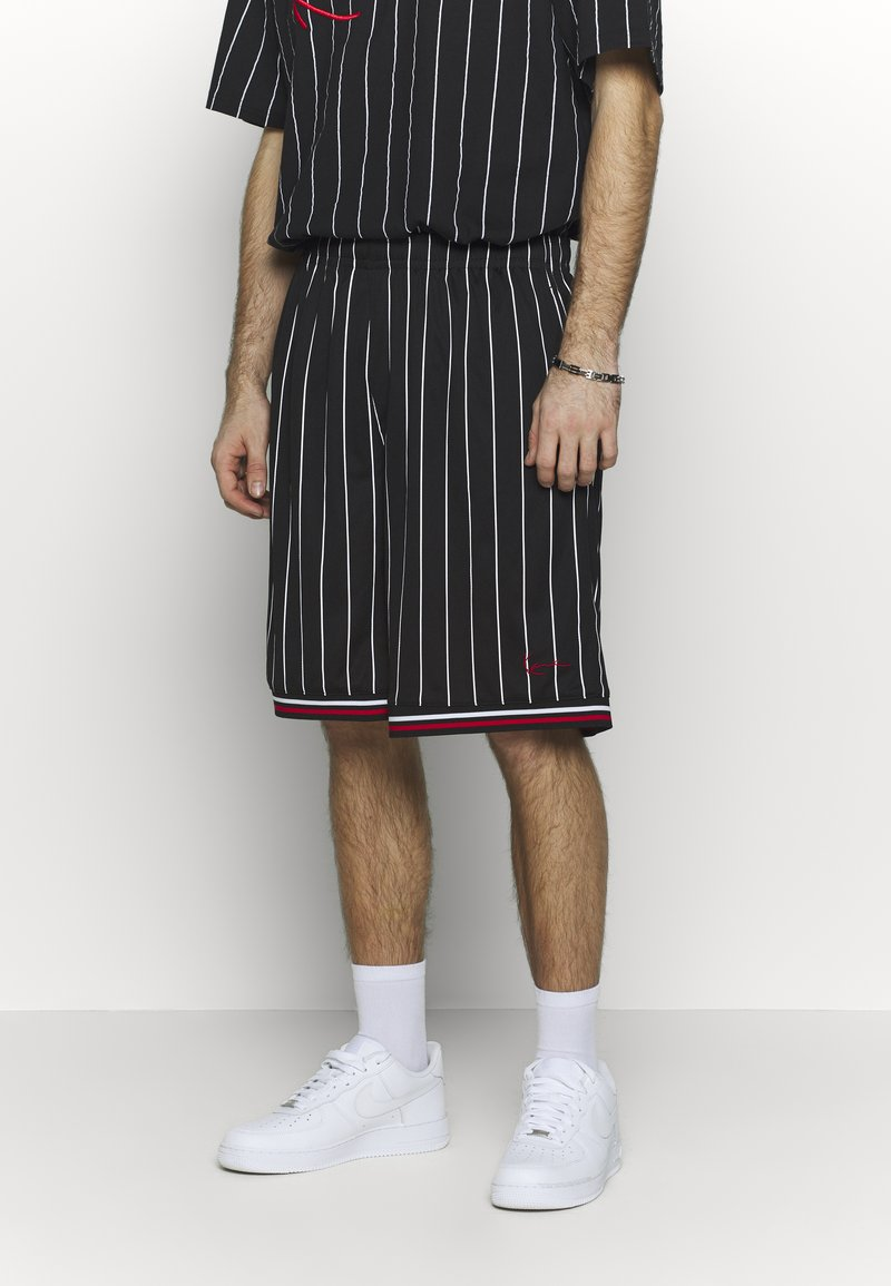 Karl Kani - SIGNATURE - Tracksuit bottoms - black/white/red