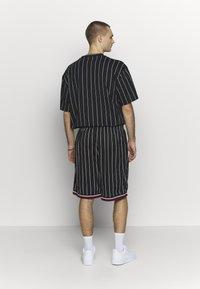 Karl Kani - SIGNATURE - Tracksuit bottoms - black/white/red - 2