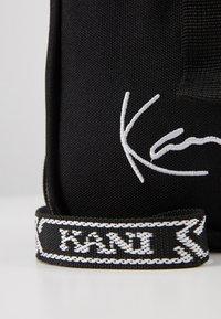 Karl Kani - SIGNATURE TAPE MESSENGER BAG - Taška spříčným popruhem - black/white - 2