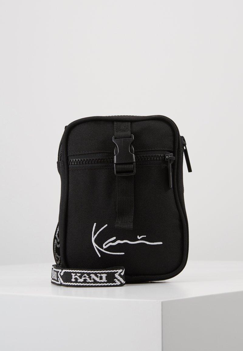 Karl Kani - SIGNATURE TAPE MESSENGER BAG - Taška spříčným popruhem - black/white