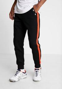Lacoste Sport - PANT TAPERED - Pantalon de survêtement - black/corrida - 0