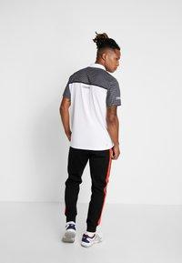 Lacoste Sport - PANT TAPERED - Pantalon de survêtement - black/corrida - 2