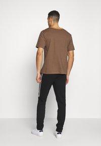 Lacoste - Pantalon de survêtement - black/white - 2