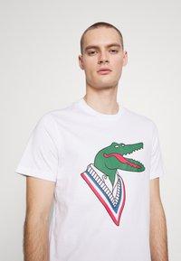 Lacoste - Unisex Lacoste x Jean-Michel Tixier Design Cotton T-shirt - Triko spotiskem - blanc/rouge - 4