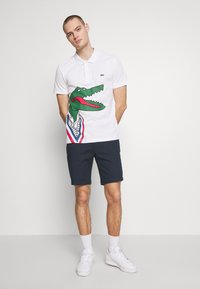 Lacoste - Unisex Lacoste x Jean-Michel Tixier Print Classic Fit Polo Shirt - Polo - blanc/rouge - 1
