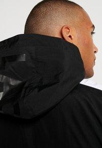 Lacoste - Lehká bunda - black/illumination/white - 3