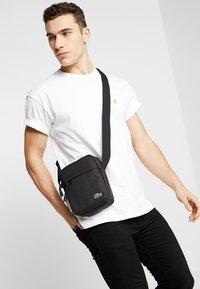 Lacoste - VERTICAL CAMERA BAG - Across body bag - black - 1