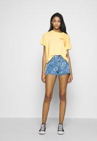 Levi's® - GRAPHIC VARSITY TEE - T-shirts med print - yellow - 1