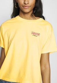 Levi's® - GRAPHIC VARSITY TEE - T-shirts med print - yellow - 4
