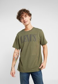 Levi's® - RELAXED GRAPHIC TEE - T-shirt z nadrukiem - 90's serif logo olive night - 0