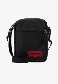 Levi's® - MINI CROSSBODY SOLID BATWING - Torba na ramię - regular black - 1