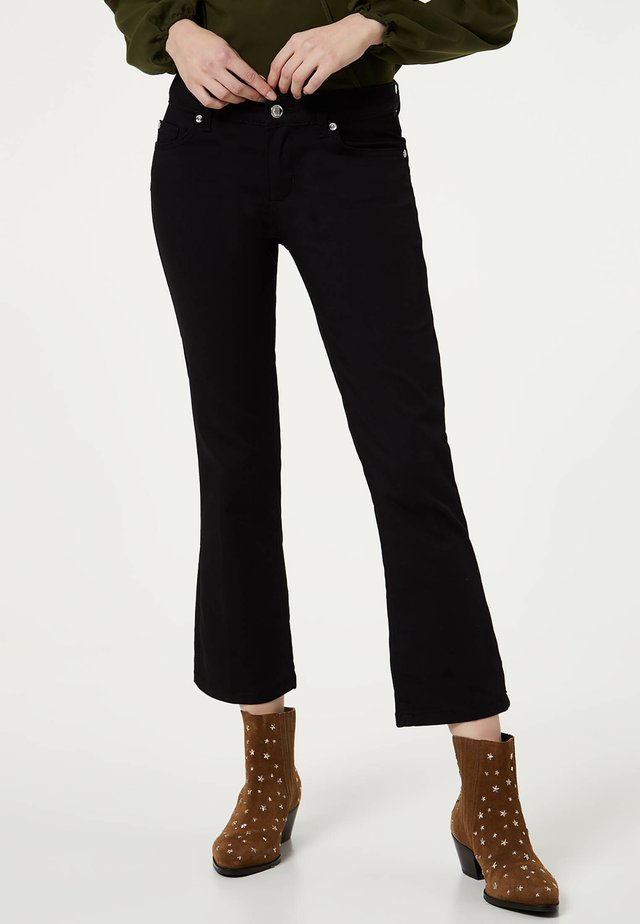 TRUMPET - Flared Jeans - black