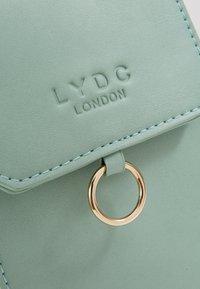 LYDC London - Taška spříčným popruhem - green - 2