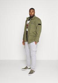 Burton Menswear London - BIG CORE CARGO JOGGER - Tracksuit bottoms - grey marl - 1