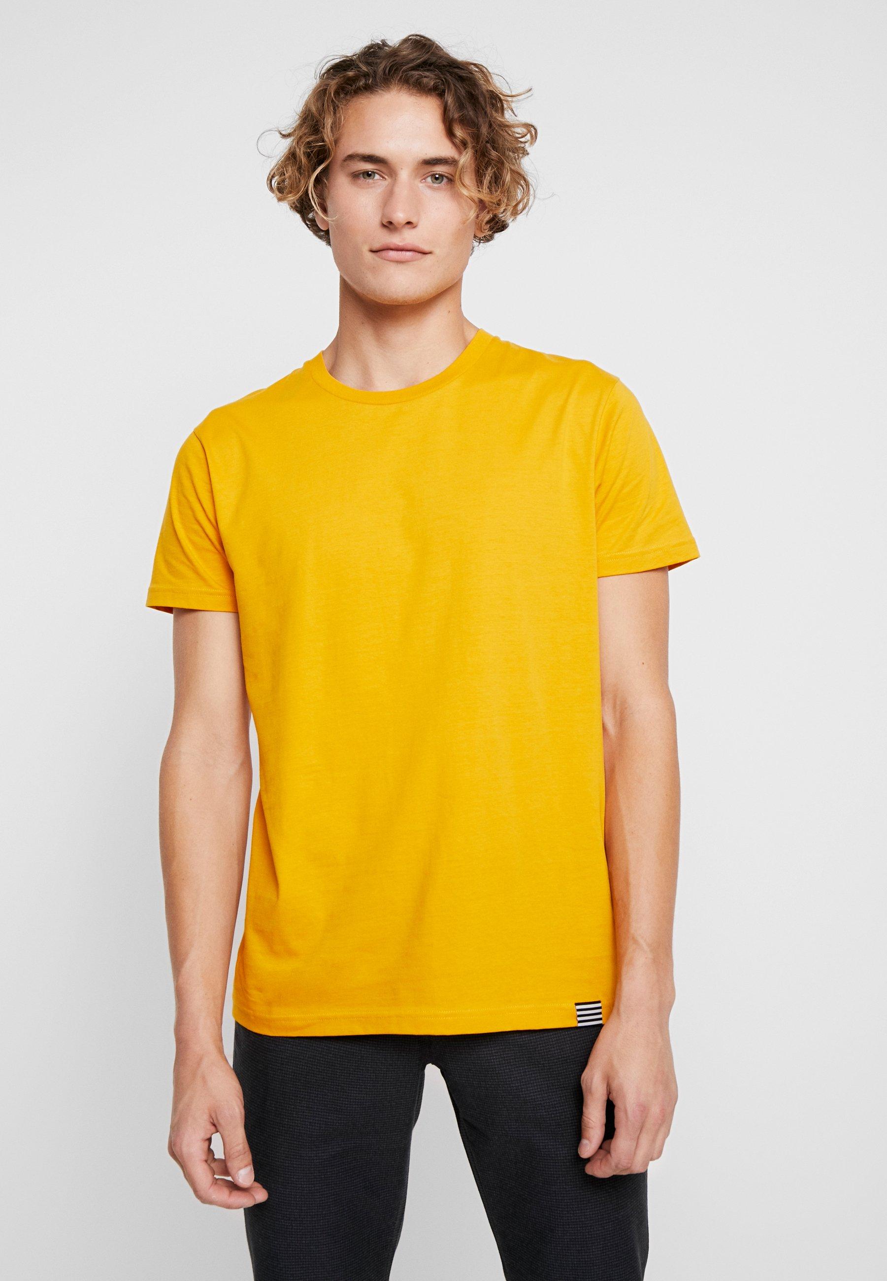Camiseta amarilla y pantalón negro