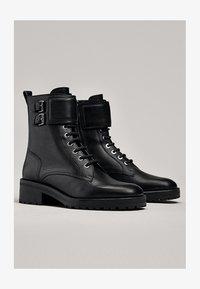 Massimo Dutti - STIEFELETTEN MIT SCHNÜRUNG UND SCHNALLEN 11112550 - Lace-up ankle boots - black - 1