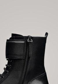 Massimo Dutti - STIEFELETTEN MIT SCHNÜRUNG UND SCHNALLEN 11112550 - Lace-up ankle boots - black - 6
