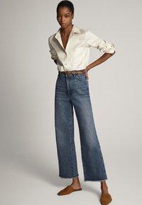 Massimo Dutti - MIT HOHEM BUND UND AUSGEFRANSTEM SAUM  - Flared Jeans - blue - 1