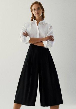 FLIESSENDER - Shorts - black