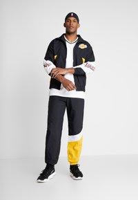 Mitchell & Ness - MIDSEASON PANT - Pantalon de survêtement - black/yellow - 1