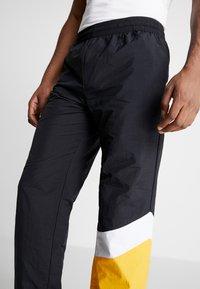 Mitchell & Ness - MIDSEASON PANT - Pantalon de survêtement - black/yellow - 3