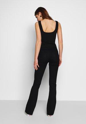 HANNIA - Flared Jeans - black