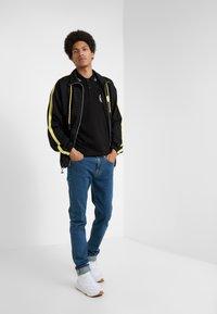 McQ Alexander McQueen - MISMATCHED STRUMMER - Jeans slim fit - indaco - 1