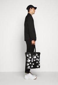 McQ Alexander McQueen - MAGAZINE TOTE SWALLOW - Tote bag - black - 0