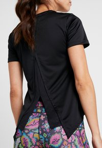 Nike Performance - TOP FEMME - T-shirt print - black/hyper pink - 4