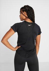 Nike Performance - TOP GLAM - T-shirt con stampa - black/metallic gold - 2