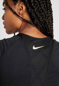 Nike Performance - TOP GLAM - T-shirt con stampa - black/metallic gold - 5