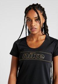 Nike Performance - TOP GLAM - T-shirt con stampa - black/metallic gold - 3