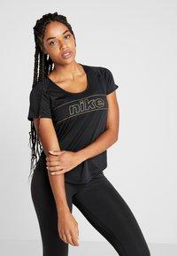 Nike Performance - TOP GLAM - T-shirt con stampa - black/metallic gold - 0