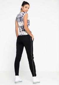 Nike Performance - Tracksuit bottoms - black/white/white - 2
