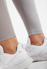 Nike Performance - FAST GLAM DUNK - Leggings - atmosphere grey/metallic gold