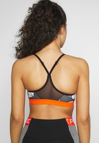 Nike Performance - MARKER PRT - Sports bra - black/safety orange - 2