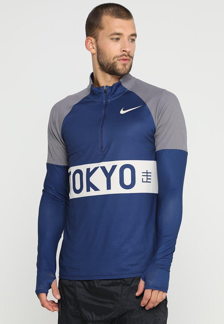 Nike Performance - NKTOP HZ TOKYO - Camiseta de deporte - thunder blue/desert sand